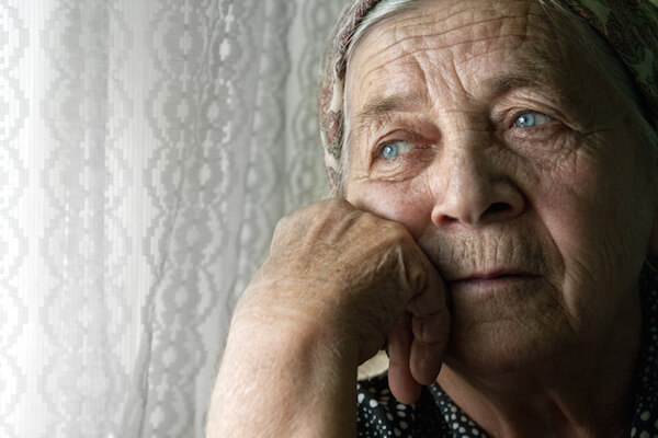Sad, elderly woman looking out the window suffering from nursing home neglect.