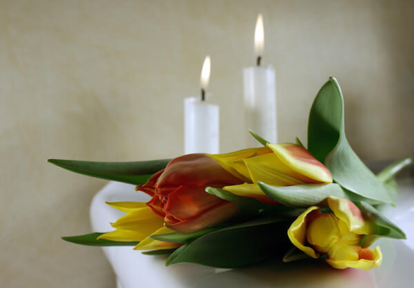 White candles with yellow and red tulips on a table after a medical malpractice incident.